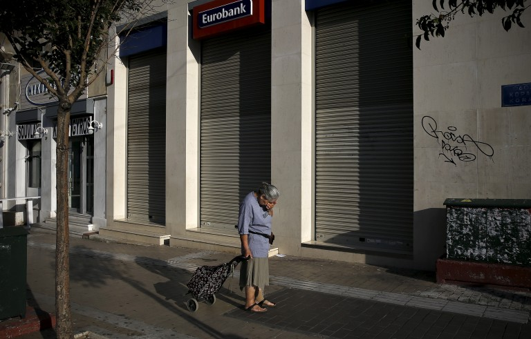 A woman pulling a shopping cart reacts outside a closed Eurobank branch in Athens, Greece June 29, 2015. Greece closed its banks and imposed capital controls on Sunday to check the growing strains on its crippled financial system, bringing the prospect of being forced out of the euro into plain sight.   REUTERS/Alkis Konstantinidis      TPX IMAGES OF THE DAY      - RTX1I76A