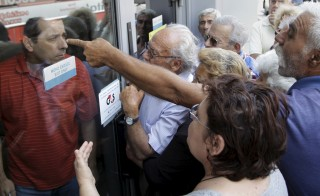 Pensioners waiting outside a closed National Bank branch and hoping to get their pensions, argue with a bank employee (L) in Iraklio on the island of Crete, Greece June 29, 2015. Greeks struggled to adjust to shuttered banks, closed cash machines and a climate of rumours and conspiracy theories on Monday as a breakdown in talks between Athens and its creditors plunged the country deep into crisis.    REUTERS/Stefanos Rapanis      TPX IMAGES OF THE DAY      - RTX1I943