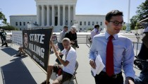 A news assistant runs to his co-workers with copies of court decisions past anti-death penalty demonstrators in front of the U.S. Supreme Court building in Washington June 29, 2015. The Supreme Court on Monday ruled that a drug used by Oklahoma as part of its lethal injection procedure does not violate the U.S. Constitution's ban on cruel and unusual punishment, dealing a setback to opponents of the death penalty.  REUTERS/Jonathan Ernst- RTX1IAAJ