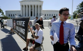 A news assistant runs to his co-workers with copies of court decisions past anti-death penalty demonstrators in front of the U.S. Supreme Court building in Washington June 29, 2015. The Supreme Court on Monday ruled that a drug used by Oklahoma as part of its lethal injection procedure does not violate the U.S. Constitution's ban on cruel and unusual punishment, dealing a setback to opponents of the death penalty.  REUTERS/Jonathan Ernst    - RTX1IAAJ