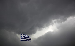 A Greek national flag flutters atop a building as dark clouds fill the sky in Athens, Greece, June 30, 2015. Greece's conservative opposition warned on Tuesday that Sunday's vote over international bailout terms would be a referendum over the country's future in Europe, and that wages and pensions would be threatened if people were to reject the package.    REUTERS/Alkis Konstantinidis  - RTX1IH7S
