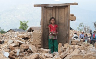 Pabitrya Paudyal, 13, holds a book that she found among the rubble of destroyed Chaturmala Higher Secondary School in Muchowk, Gorkha, one of the severely earthquake-impacted districts in Nepal on May 29. Photo courtesy of UNICEF