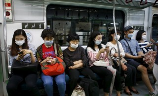 Passengers wearing masks to prevent contracting Middle East Respiratory Syndrome (MERS) sit inside a train in Seoul, South Korea, on June 5, 2015. Photo by Kim Hong-Ji/Reuters