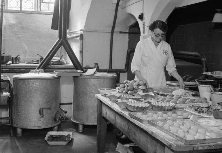 """In the 600 year old vaulted kitchen of the American Red Cross Service Club at the Bishop's Palace in Norwich, Mrs Babstock the cook sets out doughnuts, cakes and pastries on trays, ready to serve to the hungry American service personnel staying at the Club. Prior to working at the Club, Mrs Babstock was the supervisor of the British Restaurant in Warwick. According to the original caption, the British have """"provided modern gas cookers, hot plates, washing machines, dough mixers, waffle machines, and a first class kitchen staff"""" as part of the Reciprocal Aid Agreement."""
