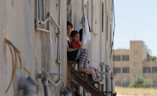 Syrian refugee children, who have been living in Jordan with their family for 2.5 years after fleeing the violence in their Syrian hometown of Idlib, sit in front of their family residence in Madaba city July 9, 2015. The number of Syrian refugees in neighboring countries has passed 4 million, the U.N. refugee agency UNHCR said on Thursday. Photo by Muhammad Hamed/Reuters