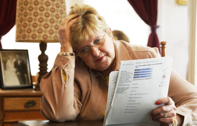 Senior woman reading Social Security form. Photo by Jim McGuire/Getty Images