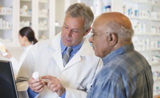 Pharmacist talking to customer about prescription Photo by Getty Images