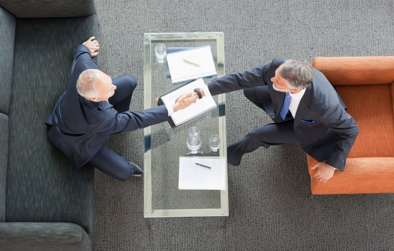 Businessmen shaking hands across coffee table in lobby. Photo by Getty Images