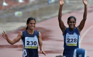 Women's 200 meters respective silver and bronze medal winners from India Asha Roy (R) and Dutee Chand wave to the crowd after their race on the fifth and the final day of the Asian Athletics Championship 2013 at the Chatrapati Shivaji Stadium in Pune on July 7, 2013. AFP PHOTO/Manjunath KIRAN        (Photo by Manjunath Kiran/AFP/Getty Images)
