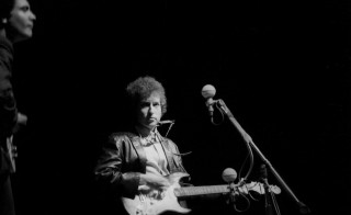 Bob Dylan plays a Fender Stratocaster electric guitar for the first time on stage as he performs at the Newport Folk Festival with guitarist Mike Bloomfield on July 25, 1965 in Newport, Rhode Island. Photo by Alice Ochs/Michael Ochs Archives/Getty Images