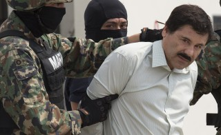 "Drug trafficker Joaquin ""El Chapo"" Guzman is escorted to a helicopter by Mexican security forces at Mexico's International Airport in Mexico city, Mexico, on Saturday, Feb. 22, 2014, during his re-arrest. Photo by Susana Gonzalez/Bloomberg via Getty Images"