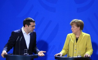 Alexis Tsipras, Greece's prime minister, left, speaks as Angela Merkel, Germany's chancellor, looks on during a news conference at the Chancellery in Berlin, Germany, on Monday, March 23, 2015. Merkel is prepared for a wide-ranging conversation with Tsipras, as Greece braces for another payment deadline within days. Photographer: Krisztian Bocsi/Bloomberg via Getty Images