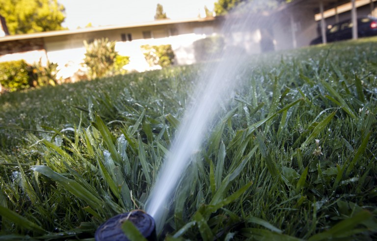 A sprinkler system over-waters grass during an early morning conservation patrol of water use by the City of Sacramento Water Conservation Office in Sacramento, California, U.S., on Wednesday, June 3, 2015. California's epic drought, four years old and seemingly endless, is getting on people's nerves. Regulators issued rules last month for cutbacks that Governor Jerry Brown ordered in April, marking the first time all the state's 39 million inhabitants have been forced to conserve. Photographer: Patrick T. Fallon/Bloomberg via Getty Images