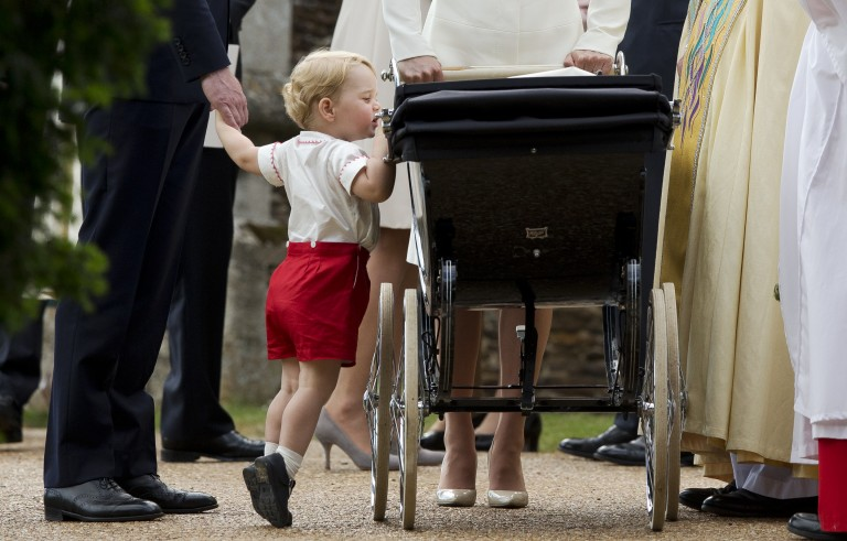 Catherine, Duchess of Cambridge, and Prince William, Duke of Cambridge, stand as Prince George looks into Princess Charlotte's pram as they leave the Church of St. Mary Magdalene on the Sandringham Estate after the Christening of Princess Charlotte of Cambridge on July 5, 2015 in King's Lynn, England.  Photo by Matt Dunham/Pool/Getty Images
