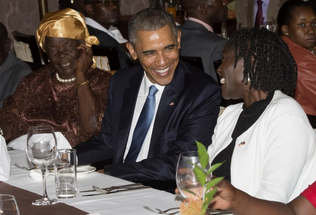 US President Barack Obama sits alongside his step-grandmother, Mama Sarah (L) and half-sister Auma Obama (R), during a gathering of family at his hotel in Nairobi, Kenya, July 24, 2015.  US President Barack Obama arrived in the Kenyan capital Nairobi late Friday, making his first visit to the country of his father's birth since his election as president. Obama was greeted by Kenyan President Uhuru Kenyatta with a handshake and embrace as he stepped off Air Force One, at the start of a weekend visit during which he will address an entrepreneurship summit and hold talks on trade and investment, counter-terrorism, democracy and human rights.  AFP PHOTO / SAUL LOEB        (Photo credit should read SAUL LOEB/AFP/Getty Images)