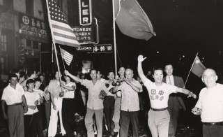 A crowd marches through New York's Chinatown to celebrate the end of World War II, V-J Day, waving American and Chinese flags on Aug. 1, 1945. Photo by Weegee (Arthur Fellig)/International Center of Photography/Getty Images