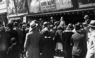 A crowd gathers around an announcer at a sideshow on the boardwalk at Coney Island in the 1930s Photo by A. E. French/Archive Photos/Getty Images