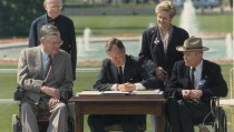 George Bush signs the Americans with Disabilities Act of 1990; standing left  to right Reverend Harold Wilkie, Sandra Parrino of the National Council on Disability; seated left to right, Evan Kemp, Chairman of the Equal Employment and Opportunity Commission, George Bush, Justin Dart, Chairman of the 's Committee on the Employment of People with Disabilities. Washington DC, USA, 26 July 1990. (Photo by Fotosearch/Getty Images).