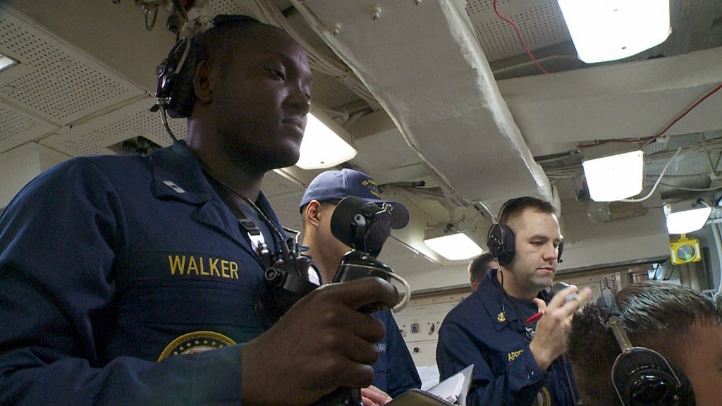 Lt. A.J. Walker, Weapons Officer, aboard the USS Pennsylvania shows the PBS NewsHour an abbreviated battle drill.  The black device that looks like a joystick for a video game is actually the training firing key used by Navy officers to practice launching nuclear armed ballistic missiles from an Ohio Class submarine. The firing key that is used to actually fire a missile is red. Photo by Dan Sagalyn