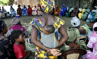 A mother carrying an infant on her back attends a meeting of women from several communities eradicating female genital mutilation, in the western Senegalese village of Diabougo, September 10, 2007. Tostan, a small Senegalese aid group credited with launching a grass roots campaign to abolish female circumcision in West Africa, will be awarded the $1.5 million Hilton Prize in New York on Wednesday. Picture taken September 10, 2007. To match feature SENEGAL-MUTILATION/CAMPAIGN    REUTERS/Finbarr O'Reilly (SENEGAL) - RTR1TR55