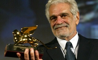 """Egyptian actor Omar Sharif holds up the Golden Lion lifetime achievment award at the Venice Film Festival August 29, 2003. Sharif, who stars in French director Francois Dupeyron's new film """"Monsieur Ibrahim et les fleurs du Coran"""" (""""Mr. Ibrahim and the Flowers of the Koran"""") premiering at the 60th edition of the festival, said the event marked a """"comeback"""" for him. REUTERS/Tony GentileTG/FMS - RTR2ATT"""