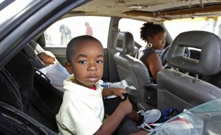 Debbie Summers (R) sits at the wheel of her car with all of their possessions inside as her children, Jordain (C), 3, and Jomari, 2, sit in the back seat as they wait for admittance to a homeless shelter at the offices of Faith in Action community housing in Fort Lauderdale, Florida, December 21, 2011. In a report issued earlier this month, the National Center on Family Homelessness, based in Needham, Massachusetts, said 1.6 million children were living on the streets of the United States last year or in shelters, motels and doubled-up with other families. That marked a 38 percent jump in child homelessness since 2007 and Ellen Bassuk, the center's president, attributes the increase to fallout from the U.S. recession and a surge in the number of extremely poor households headed by women. Picture taken December21, 2011. TO MATCH FEATURE USA-HOMELESS/ REUTERS/Joe Skipper    (UNITED STATES - Tags: SOCIETY) - RTR2VLFU