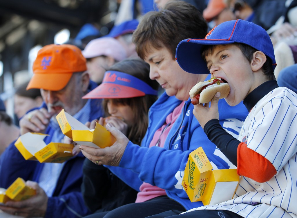 New York Mets fans enjoy hotdogs during an MLB National League opening day baseball game against the Atlanta Braves at CitiField in New York April 5, 2012.  REUTERS/Adam Hunger (UNITED STATES - Tags: SPORT BASEBALL) - RTR30DWN