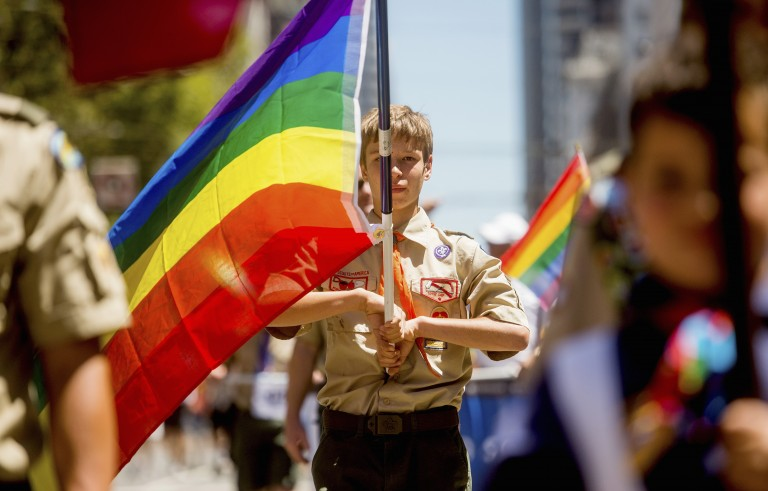 A Boy Scout carries a rainbow flag during the San Francisco Gay Pride Festival, June 29, 2014. The Boy Scouts of America is set to repeal its longstanding blanket ban on openly gay leaders Monday. Photo by Noah Berger/Reuters