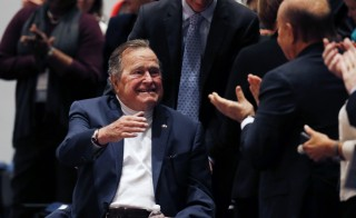 "Former United States President George H. W. Bush is brought into the auditorium where his son Former United States President George W. Bush speaks about his new book titled ""41: A Portrait of My Father"" at the George Bush Presidential Library Center in College Station, Texas November 11, 2014.  REUTERS/Bob Daemmrich/Pool (UNITED STATES - Tags: POLITICS MEDIA) - RTR4DRPC"