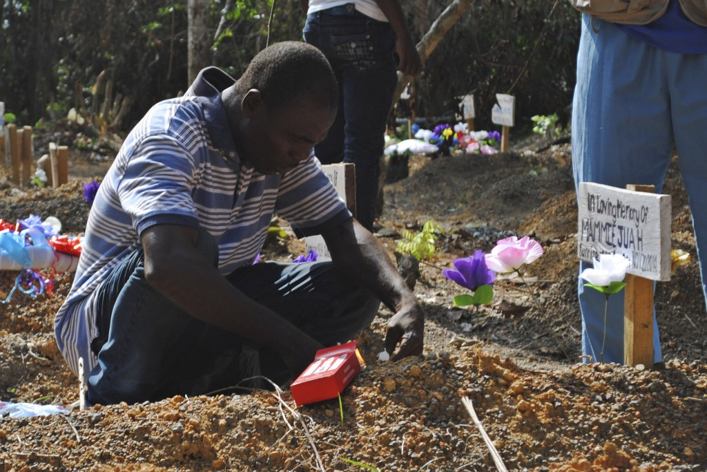 Survivor of the Ebola virus Stanley Juah visits his son's grave at a cemetery for victims of Ebola in Suakoko, Liberia on March 11. Photo by James Giahyue/Reuters