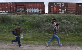 A Salvadoran father carries his son while running next to another immigrant as they try to board a train heading to the Mexican-U.S. border, in Huehuetoca, near Mexico City, June 1, 2015. An increasing number of Central Americans are sneaking across Mexico's border en route to the United States, but many of them don't end up making it very far. Picture taken June 1, 2015. Photo by Edgard Garrido/Reuters