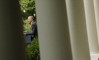 U.S. President Barack Obama is seen speaking in the Rose Garden as seen through the columns of the White House colonnade as he reacts after the Supreme Court ruled 6-3 to uphold the nationwide availability of tax subsidies that are crucial to the implementation of the Affordable Care Act at the White House in Washington June 25, 2015. Photo by Jonathan Ernst/Reuters