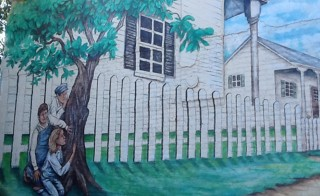 """A mural showing a scene from the 1960 bestseller """"To Kill A Mockingbird"""" was painted on a building near where the homes of 1960s writers Harper Lee and Truman Capote's homes once stood in Monroeville, Alabama on Oct. 23, 2013. Photo by Verna Gates/Reuters"""