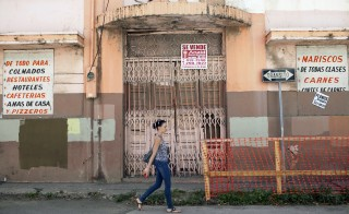 A woman walks past a closed restaurant in Ponce, on Puerto Rico's southern coast, February 5, 2014. Standard & Poor's cut Puerto Rico's credit rating to junk status, in the latest blow to an economy that has been battling chronic recession, population decline and a perennial budget shortfall that has left it with $70 billion in debt. REUTERS/Alvin Baez (PUERTO RICO - Tags: BUSINESS POLITICS) - RTX189FA