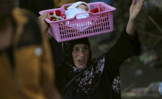 An Iraqi Sunni displaced woman, who fled the violence in the city of Ramadi carries her child on the outskirts of Baghdad, Iraq May 19, 2015. Iraqi security forces on Tuesday deployed tanks and artillery around Ramadi to confront Islamic State fighters who have captured the city in a major defeat for the Baghdad government and its Western backers. REUTERS/Stringer - RTX1DP53