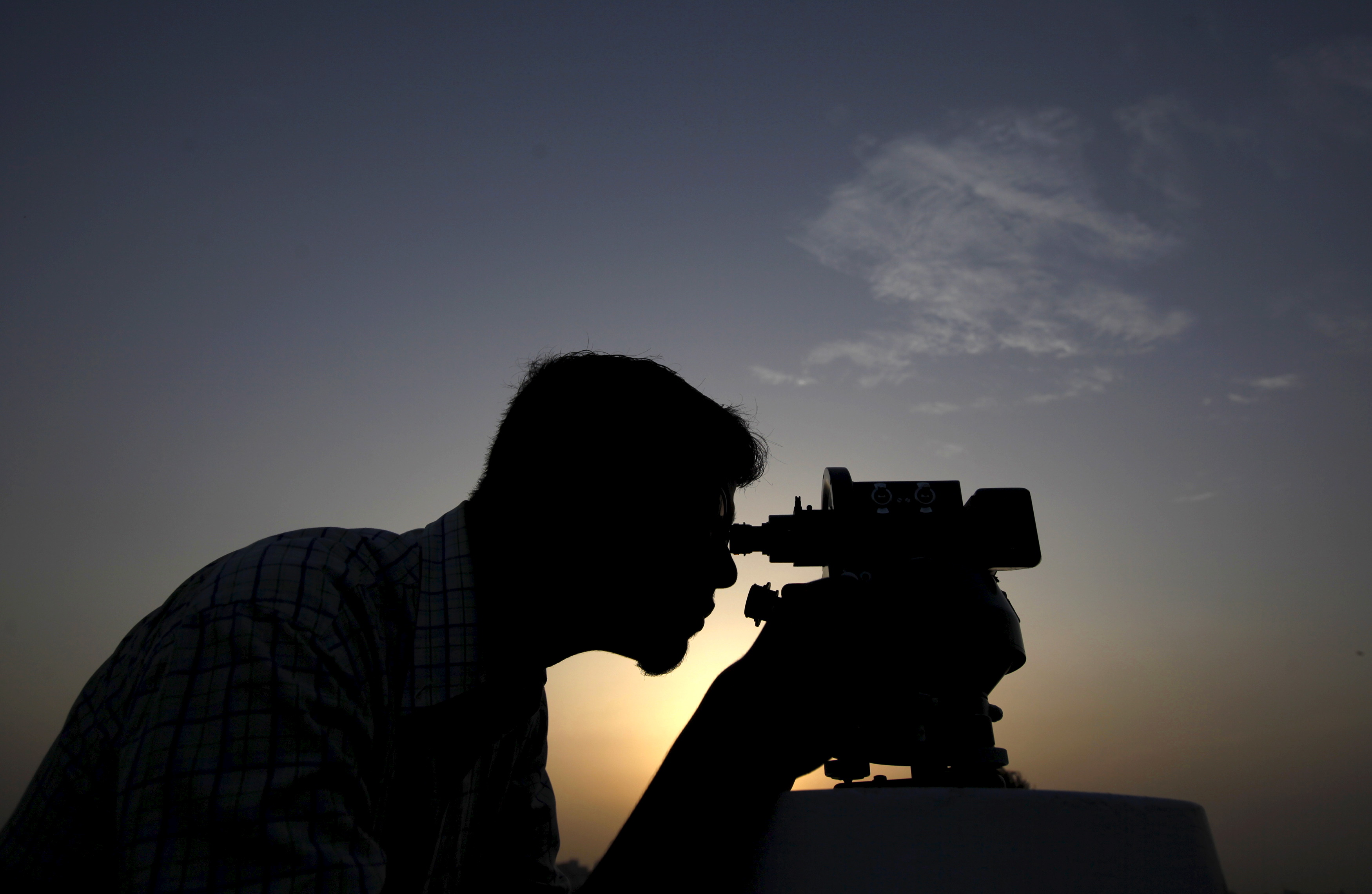 A man is silhouetted as he adjusts a theodolite to look for the new moon that will mark the start of Ramadan, from Pakistan's Meteorological Department (PMD) in Karachi, Pakistan, June 17, 2015. The same process is used to determine the official date of Eid al-Fitr. Photo by Akhtar Soomro/Reuters
