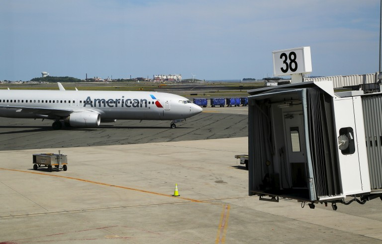 """An American Airlines plane pulls up to a gate at Logan Airport in Boston, Massachusetts, United States June 13, 2015. Outdoor scenes in Boston show local residents enjoying balmy weather amid lush greenery as the summer solstice approaches on 21 June. The very same locations suffered heavy snowstorms last winter, with snow ploughs, skiers and snowboarders battling the drifts. Boston got 275.8 cm of snow over the winter, the most since 1872, when records began. A few months after the snowstorms, Brian Snyder revisited the same places and shot pictures at exactly the same locations. REUTERS/Brian SnyderPICTURE 30 OF 30 FOR WIDER IMAGE STORY """"WINTER FREEZE, SUMMER SOLSTICE"""" SEARCH """"BRIAN SOLSTICE"""" FOR ALL IMAGES - RTX1H85Y"""