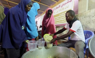 Somali families receive an Iftar (breaking of fast) meal from a Qatari charity organization during the holy Muslim month of Ramadan in Mogadishu, June 22, 2015. Photo by Feisal Omar/Reuters