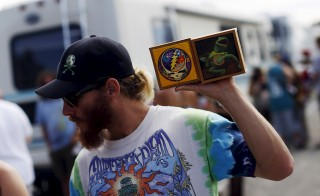 "A fan holds handmade memorabilia in the parking lot before Grateful Dead's ""Fare Thee Well"" tour in Santa Clara, California, last month. Photo by Stephen Lam/Reuters"