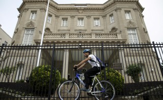 A cyclist pedals past the Cuban Interests Section is seen in Washington earlier this month. Today, the diplomatic missions of each country are upgraded from interests sections to embassies. Photo by Gary Cameron/Reuters