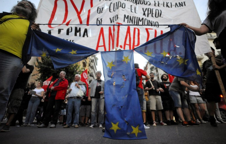 Anti-EU protesters hold a burned and torn European Union flag during a protest at the northern city of Thessaloniki, Greece July 1, 2015. A defiant Prime Minister Alexis Tsipras urged Greeks on Wednesday to reject an international bailout deal, wrecking any prospect of repairing broken relations with EU partners before a referendum on Sunday that may decide Greece's future in Europe. REUTERS/Alexandros Avramidis - RTX1INYK