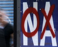A referendum campaign poster that reads 'Yes (Nai)' is seen on a bus stop with a graffiti that reads 'No (Oxi)' on it in Athens, Greece, July 3, 2015. An opinion poll on Greece's bailout referendum published on Friday pointed to a slight lead for the Yes vote, on 44.8 percent, against 43.4 percent for the No vote that the leftwing government backs.    REUTERS/Christian Hartmann  - RTX1IUFD