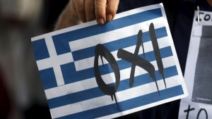 "A man holds a sign that reads, ""No"", supporting Greece during a pro-Greece protest in front of European Union office in Barcelona, Spain, July 3, 2015. REUTERS/Albert Gea - RTX1IY3L"