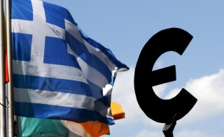 A Greek flag flies past a statue depicting the European unity outside the European Parliament ahead of a euro zone leaders summit on Greece in Brussels, Belgium, July 6, 2015. REUTERS/Francois Lenoir - RTX1J9F1