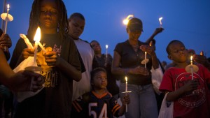People gather for a candlelight vigil against gun violence in the Englewood neighborhood in Chicago, Illinois, United States, July 3, 2015. Extra police patrols and long shifts were not enough to prevent nine deaths and about 50 injuries from gun violence in Chicago over the Fourth of July weekend, when homicides jump almost every year. Chicago, with 2.7 million people, is the most violent large city in the United States, with poverty, segregation, dozens of small street gangs, and a pervasive gun culture all contributing to the problem. Picture taken July 3, 2015.   REUTERS/Jim Young   - RTX1JA3N