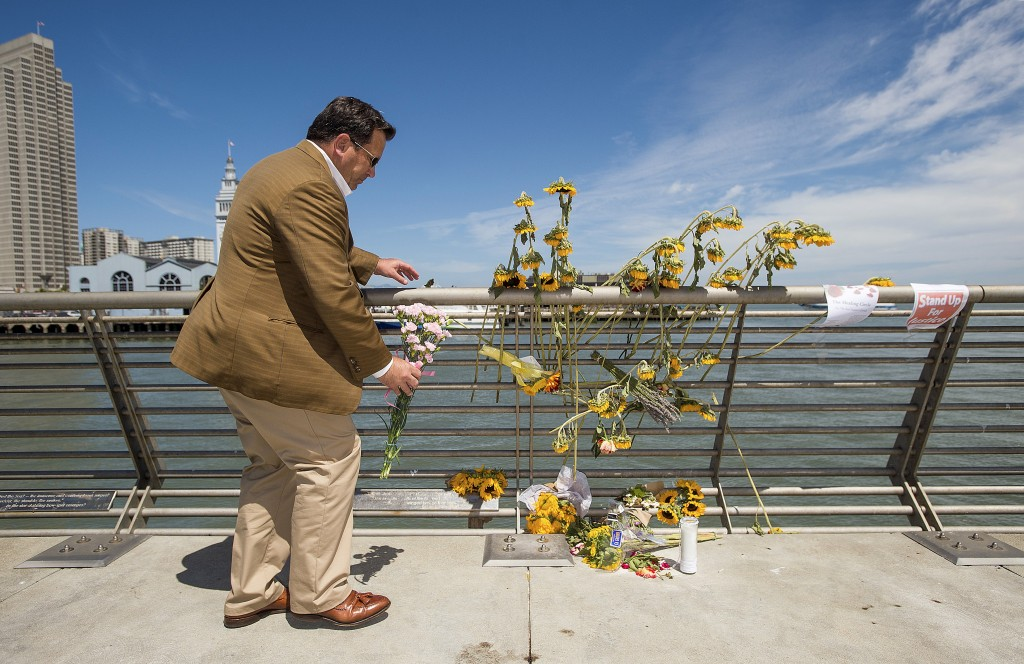 Steve, who declined to give a last name, leaves flowers at a makeshift memorial for shooting victim Kathryn Steinle on Pier 14 in San Francisco, California July 6, 2015. Steinle, 32, was fatally shot as she walked with her father along the popular Embarcadero pier on July 1, 2015 in what San Francisco police described as an apparent random attack. The random fatal shooting, allegedly by an immigrant, proves the United States must tighten its borders, according to a statement on Friday by U.S. presidential candidate Donald Trump, who is facing heavy criticism for his comments about Mexicans.   REUTERS/Noah Berger