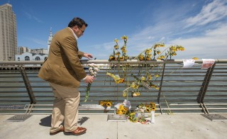 Steve, who declined to give a last name, leaves flowers at a makeshift memorial for shooting victim Kathryn Steinle on Pier 14 in San Francisco, California July 6, 2015. Steinle, 32, was fatally shot as she walked with her father along the popular Embarcadero pier on July 1, 2015 in what San Francisco police described as an apparent random attack. The random fatal shooting, allegedly by an immigrant, proves the United States must tighten its borders, according to a statement on Friday by U.S. presidential candidate Donald Trump, who is facing heavy criticism for his comments about Mexicans.   REUTERS/Noah Berger - RTX1JAR4