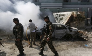 Afghan security forces walk past a burning car after a group of insurgents stormed a compound used by Afghanistan's intelligence agency in Kabul, Afghanistan, July 7, 2015. Taliban insurgents raided the compound used by Afghanistan's intelligence agency, a police spokesman said, killing one security guard and wounding another.  REUTERS/Omar Sobhani  - RTX1JDVF