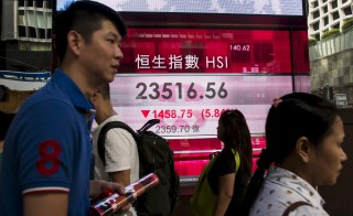 Passers-by walk in front of a panel displaying the closing Hang Seng Index and China Enterprise Index in Hong Kong, China July 8, 2015. Losses on the mainland weighed heavily on Hong Kong shares, with the Hang Seng Index down 3.3 percent and shares of Chinese companies listed in the city falling 4.2 percent. REUTERS/Tyrone Siu - RTX1JIFP