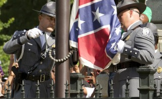 "The Confederate battle flag is permanently removed from the South Carolina statehouse grounds during a ceremony in Columbia, South Carolina July, 10, 2015. South Carolina removed the Confederate battle flag from the state capitol grounds on Friday to chants of ""USA, USA!,"" after three weeks of emotional debate over the banner, a symbol of slavery and racism to many, but of Southern heritage and pride to others. REUTERS/Jason Miczek      TPX IMAGES OF THE DAY - RTX1JWTW"